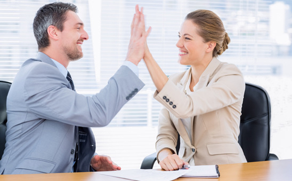 Smartly dressed young man and woman giving high five in a business meeting at office desk